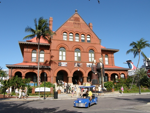 key west customs house in full glory the red brick facade dominating the street with people casually about shooting snapshots and strolling with a blue kit electric car turning around the outdoor lobby