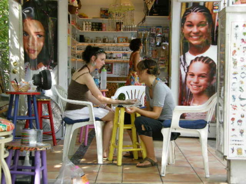 two young women casually dressed sitting in a t-shirt shop door open to the street one girl doing the nails of the other both smiling and talking