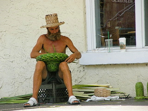 street merchant weaving baskets from palm leaves sitting shirtless on a wooden box a straw hat shading his face as he is intent on the task