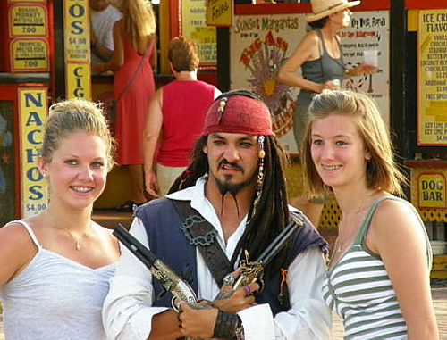 two young women at the pier flanking a busker dressed as a pirate from Pirates of the Caribbean both girls smiling