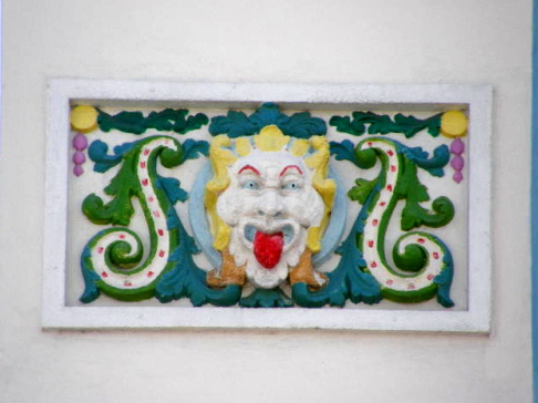 colorful bas relief of a clown eyes wide cheeks stylized and tongue from the middle to the bottom